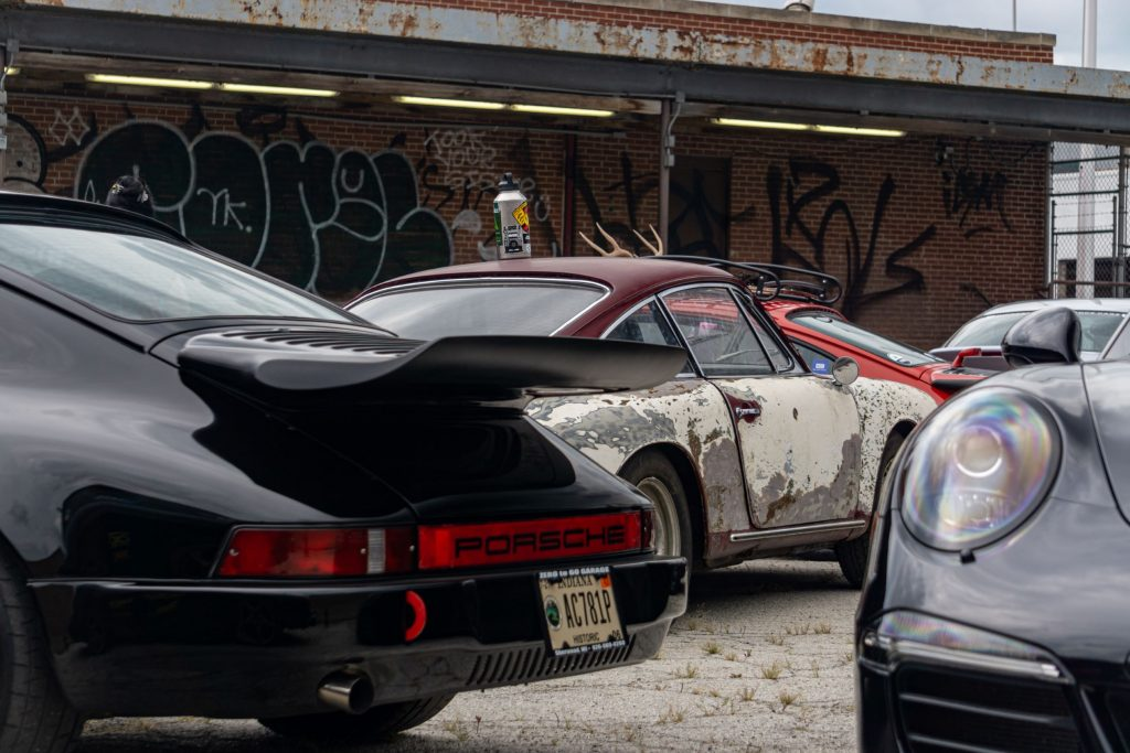 Several classic Porsche 911s with a modern Panamera in a parking lot next to a graffiti-sprayed brick wall
