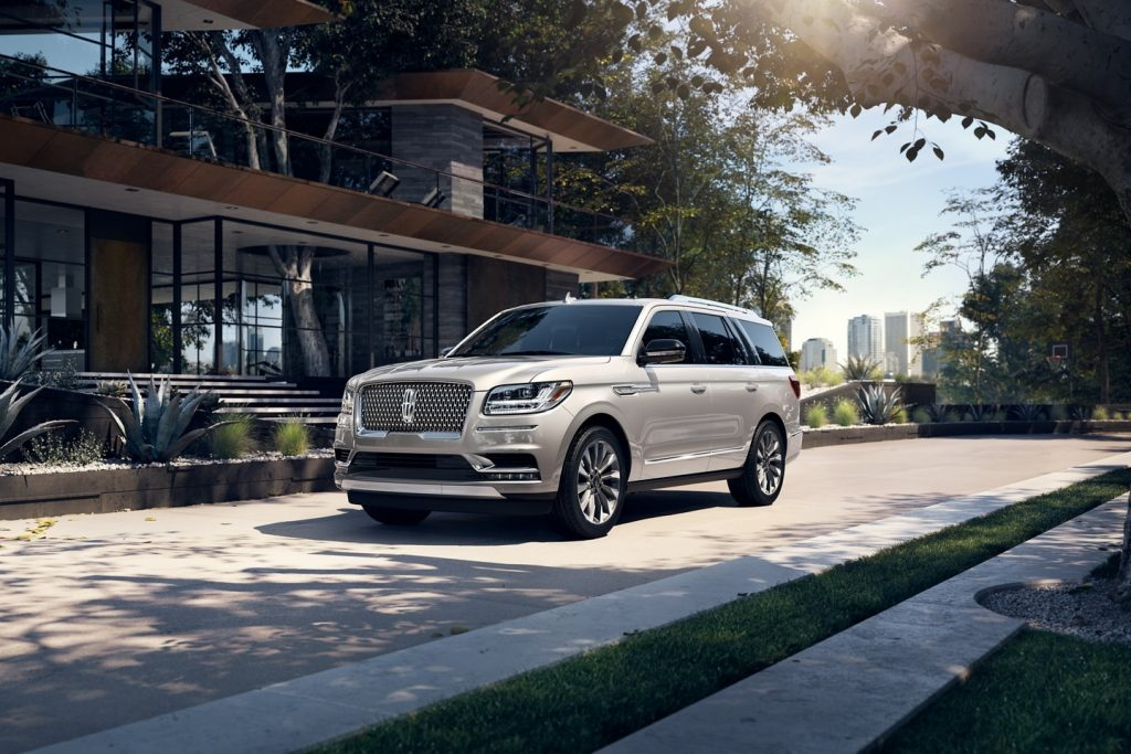 Silver 2021 Lincoln Navigator parked next to a large house
