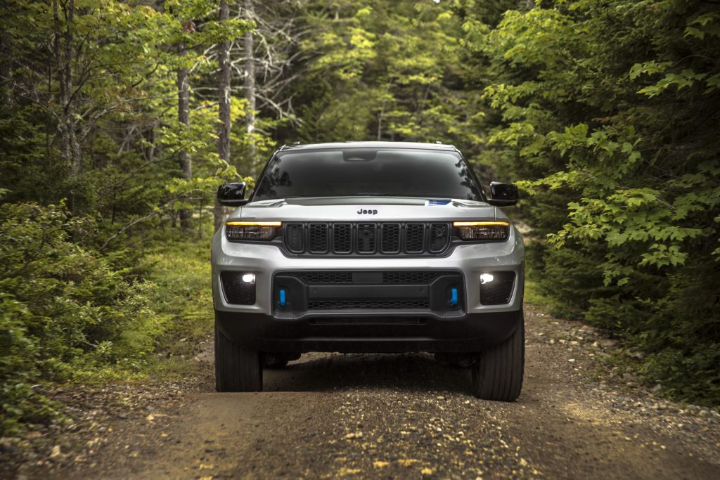 Silver 2022 Jeep Grand Cherokee 4xe driving through a forest