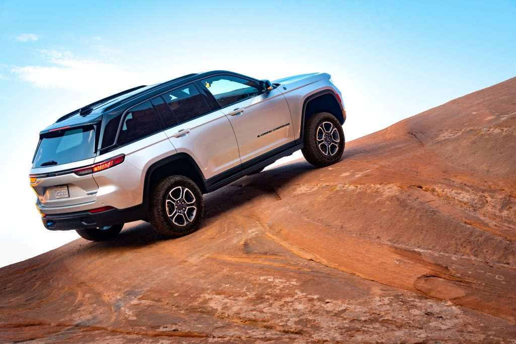 Silver 2022 Jeep Grand Cherokee 4xe driving up a hill