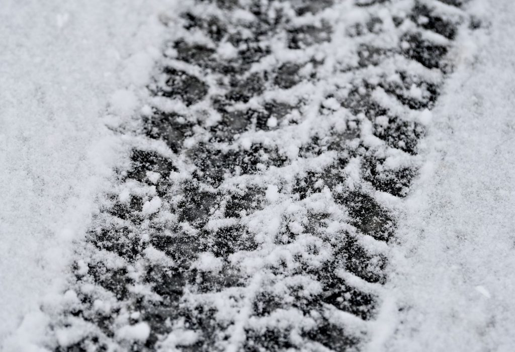A snow tire print in the snow.