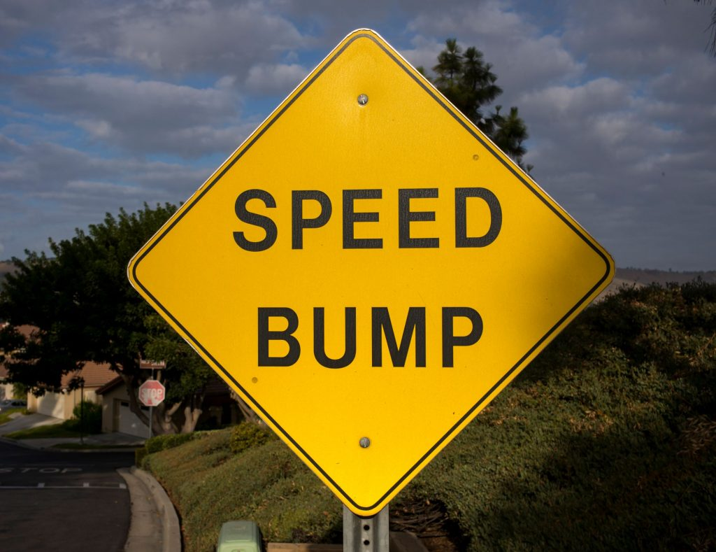 Yellow Speed Bump sign along a highway.