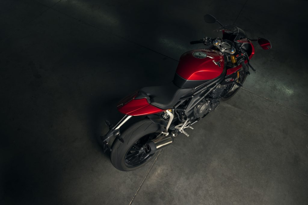 The overhead side 3/4 view of a red-and-black 2022 Triumph Speed Triple 1200 RR in a garage