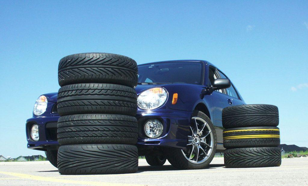 A 2003 Subaru Impreza TS2.5 parked by stacks of tires