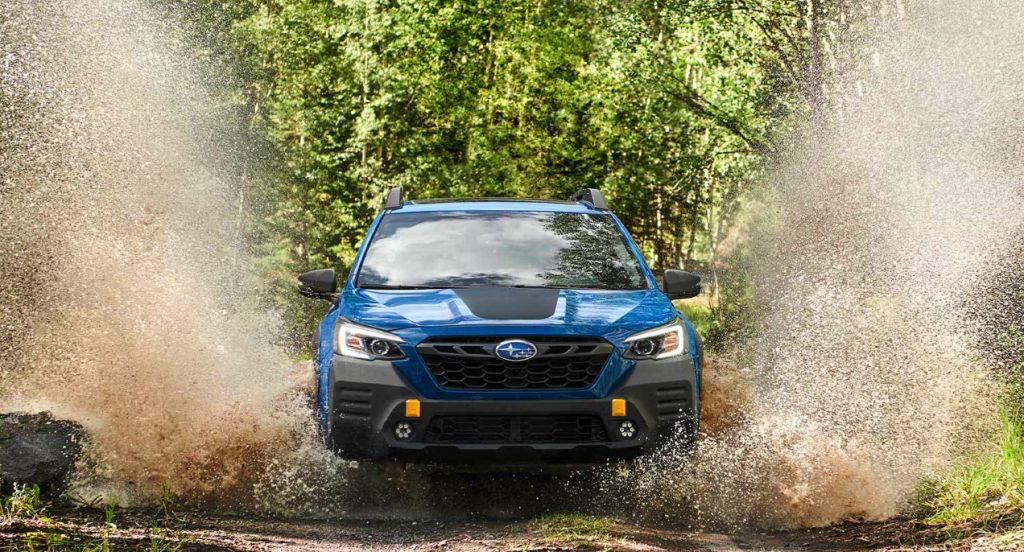 A blue Subaru Outback Wilderness is off-roading in the mud surrounded by trees with green leaves.