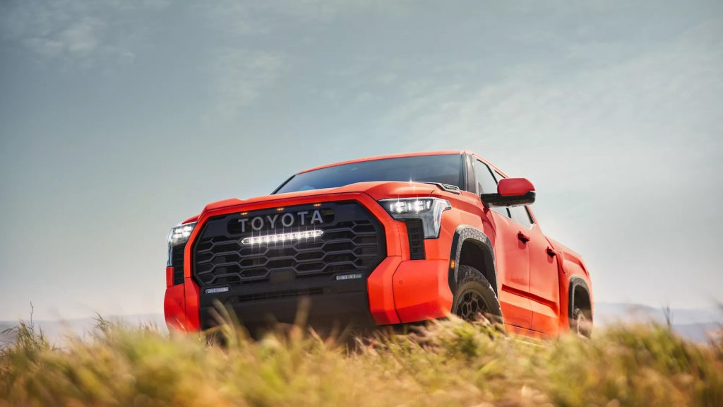 This is a promo photo of a 2022 Toyota Tundra TRD Pro parked in a field. This high-speed offroad truck is a cost-effective Ford Raptor