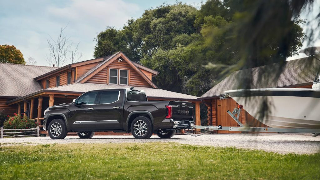 This is a promo photo of the 2022 Toyota Tundra towing capacity tested as a gray truck tows a boat.