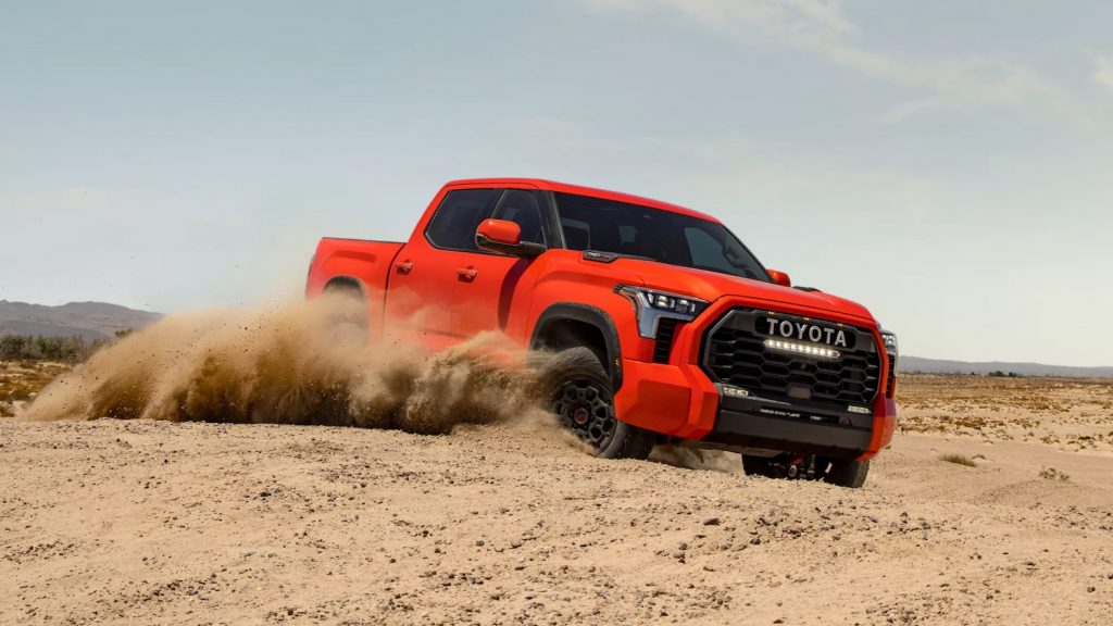 This is a promo photo of an orange 2022 Toyota Tacoma hybrid off-roading in sand.