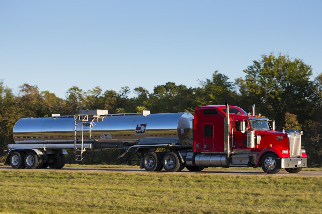 A red semi truck with wheel spikes drives down the highway hauling an oil tanker
