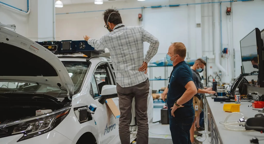 Technicians working on a white Aurora Toyota Sienna self-driving taxi
