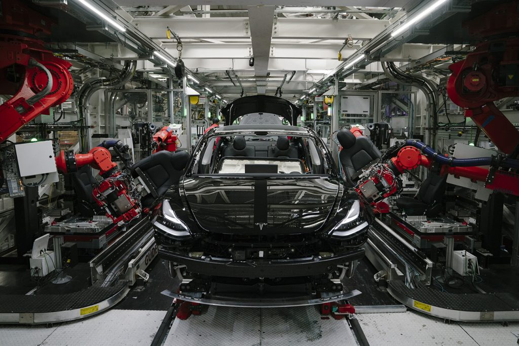 Robotics arms install the front seats to the Tesla Model 3 at the Tesla factory in Fremont, California. Tesla is one of the few automakers to not be hit hard by the global chip shortage