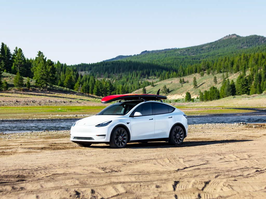 Tesla Model Y with a surfboard on the roof