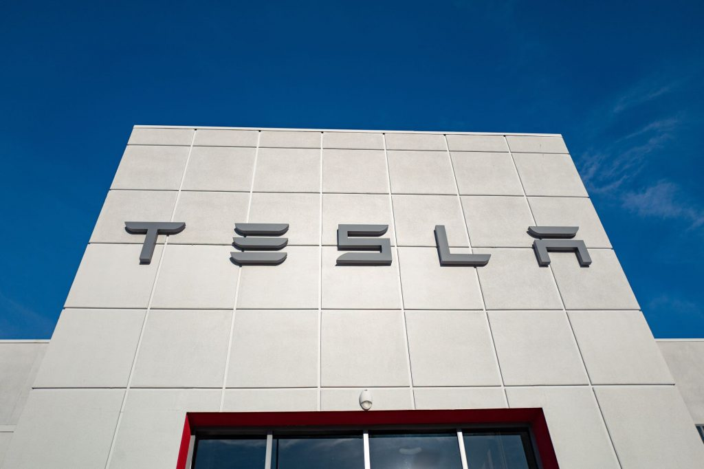 White Tesla building with Tesla written in grey against a blue sky.