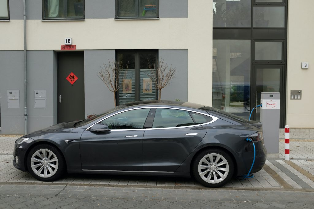 A Tesla Model S electric car charges at a public charging colum