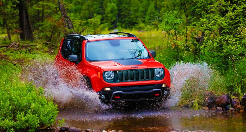 A red 2021 Jeep Renegade Trailhawk off-road SUV is driving through a shallow body of water.