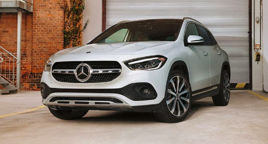 A white Mercedes-Benz GLA luxury SUV is parked outside the garage of a building.