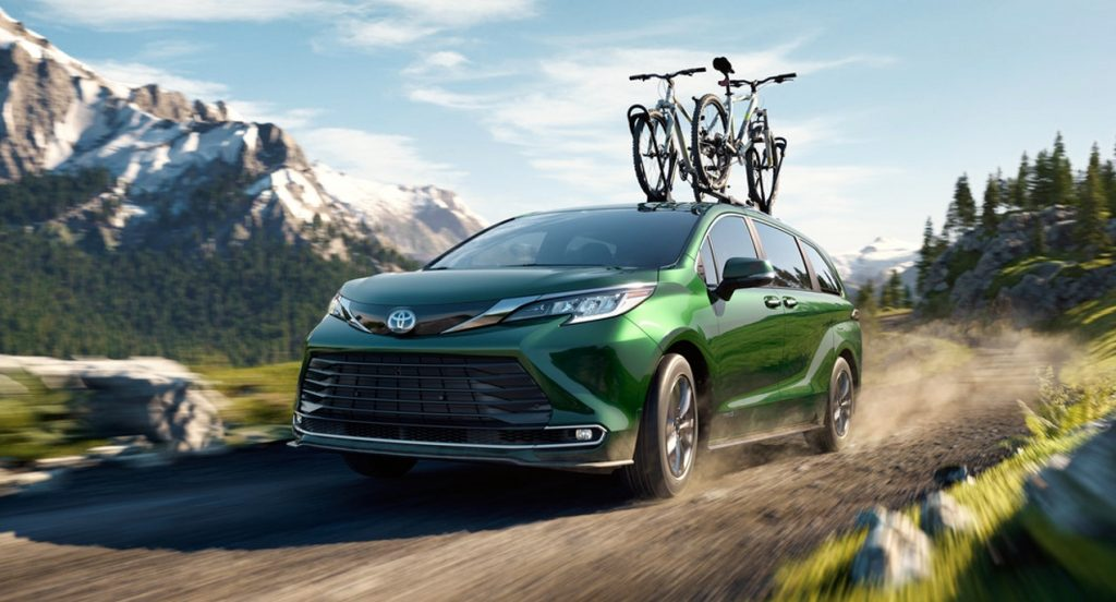 A green 2022 Toyota Sienna minivan is driving on a trail with bikes attached to its roof.
