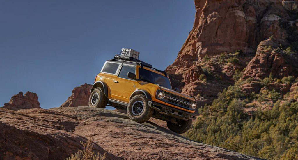 A yellow Ford Bronco small off-road SUV is driving down a mountainous hill.