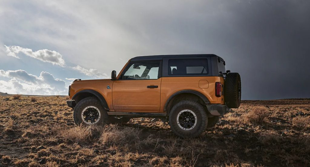 A yellow Ford Bronco small off-road SUV is off-roading.