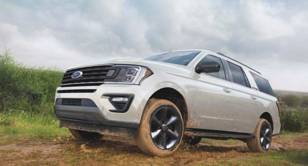 A white Ford Expedition is off-roading in the mud.
