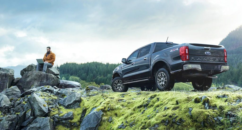 A black Ford Ranger compact pickup truck is parked on a mountain. A man is on his laptop sitting on a rock nearby.