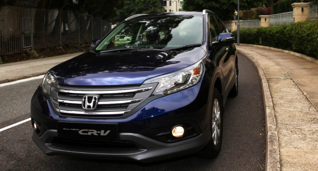 A navy blue Honda CR-V SUV is parked on a street.