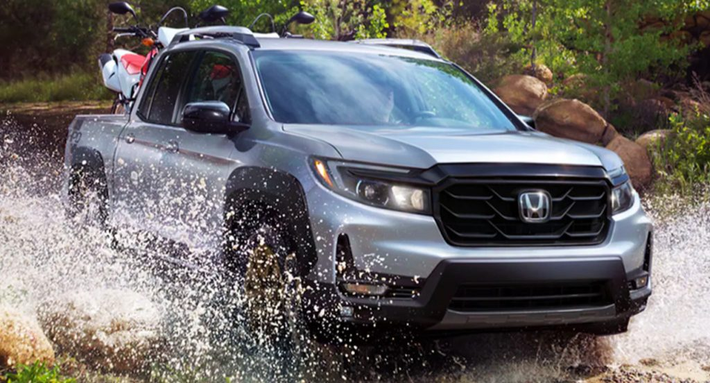A silver Honda Ridgeline crosses a small, shallow body of water while carrying two dirt bikes in its truck bed. The Honda Ridgeline truck appears to be in the wilderness.