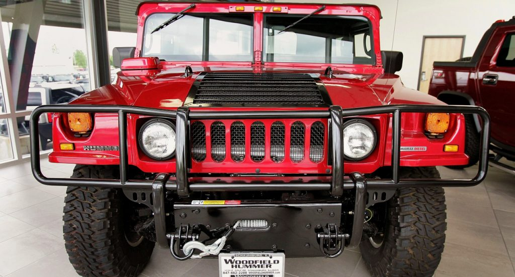A red Hummer H1 SUV is parked in a showroom.