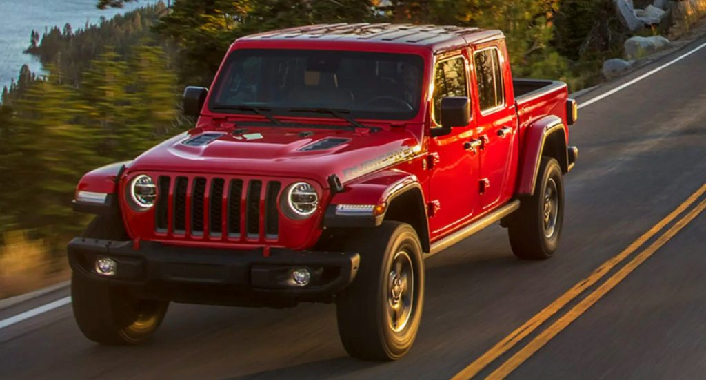 A red 2021 Jeep Gladiator pickup truck is driving on a highway.