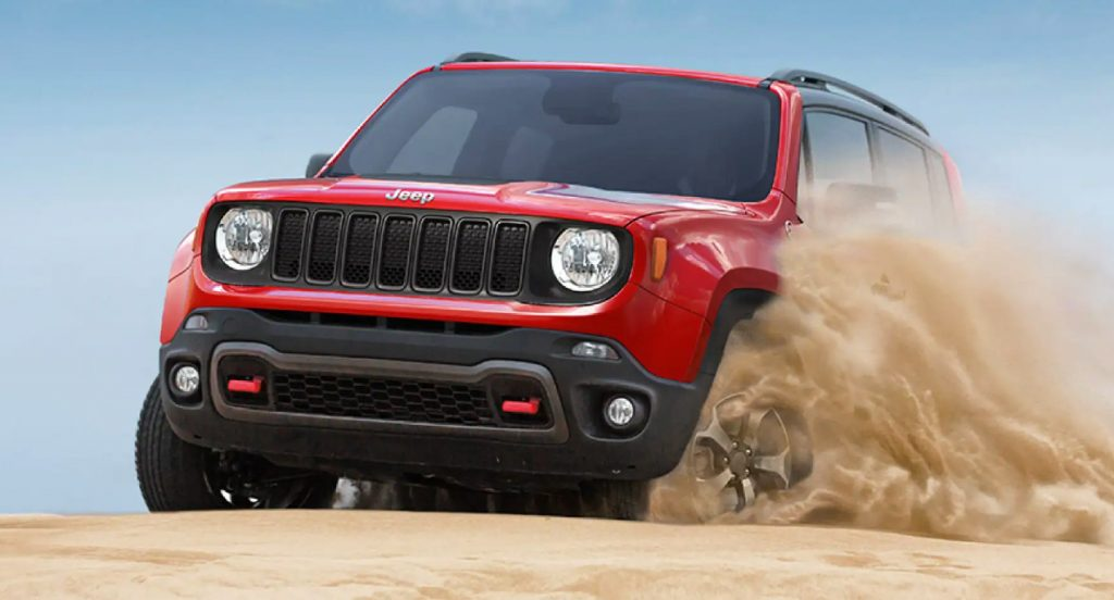 A red 2021 Jeep Renegade Trailhawk off-road SUV is driving through sand.