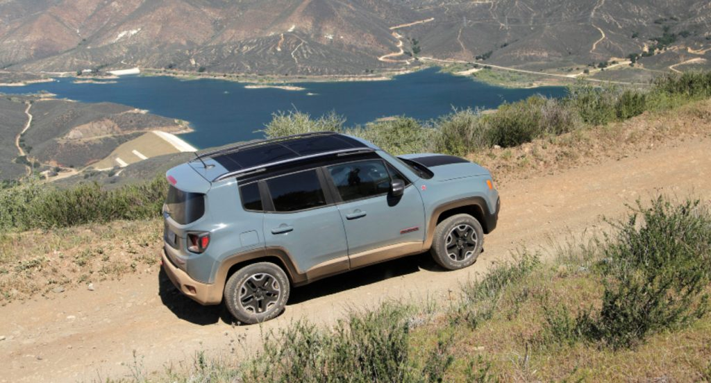 A green Jeep Renegade Trailhawk small off-road SUV is off-roading on a trail.