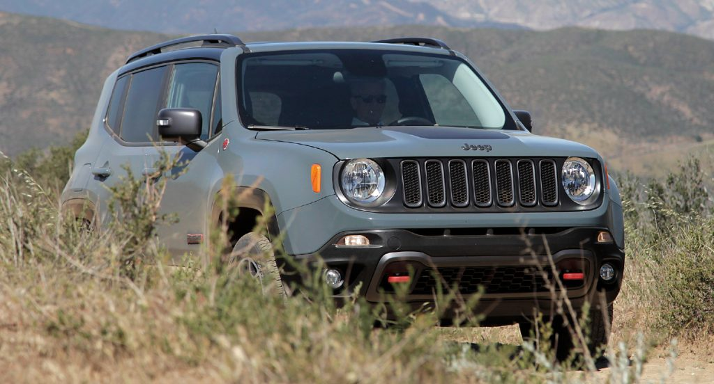 A green Jeep Renegade Trailhawk off-road SUV is in nature.