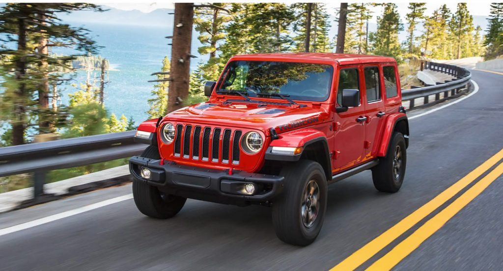 A red Jeep Wrangler is driving on the highway.