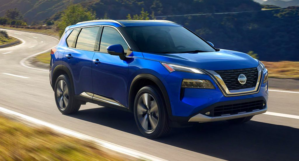 A blue 2021 Nissan Rogue compact SUV is driving on the road.