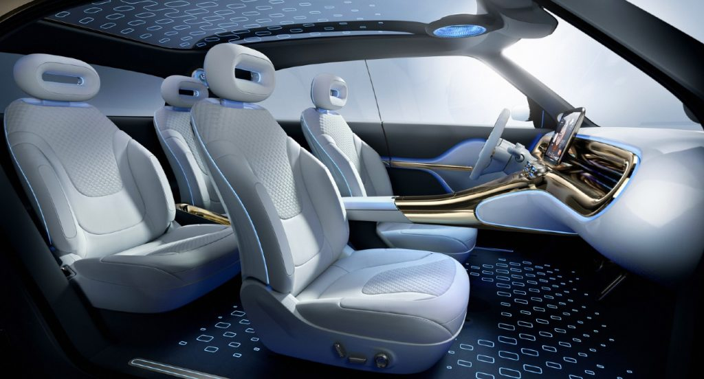 The interior of a Smart Concept #1 electric crossover vehicle. The roof of the vehicle is made of transparent glass. There is a bright blue highlight around the seats and dashboard.