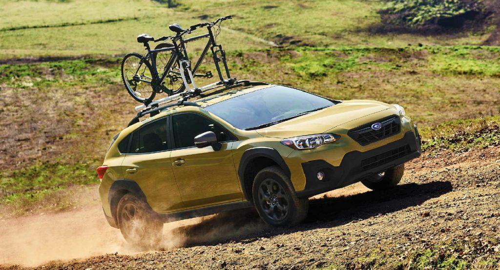 A yellow Subaru Crosstrek small off-road SUV is off-roading on a trail.