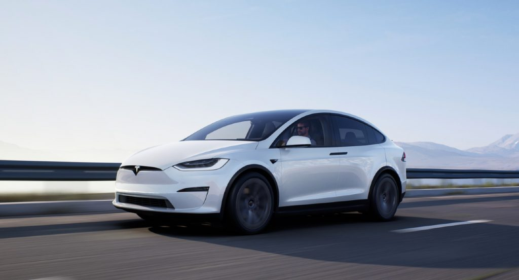 A white Tesla Model X SUV is driving on a highway.