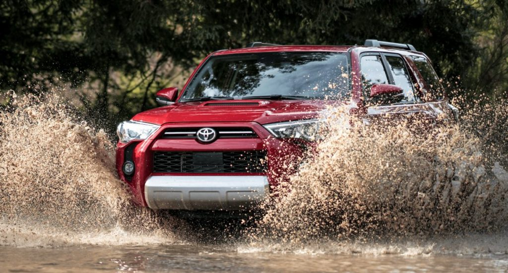 A red Toyota 4Runner SUV is driving through the mud.