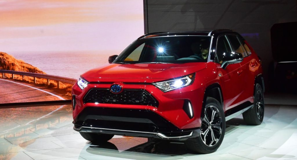 A red Toyota RAV4 Prime SUV is on display.