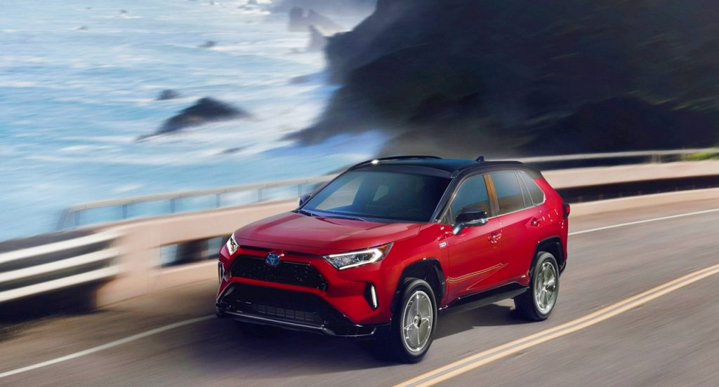 A red Toyota RAV4 Prime is driving on a highway alongside the ocean.
