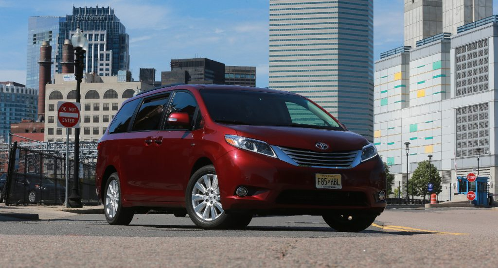 A red Toyota Sienna minivan is parked in the middle of a city street.