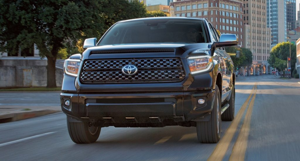 A black Toyota Tundra is driving down the street in a city.