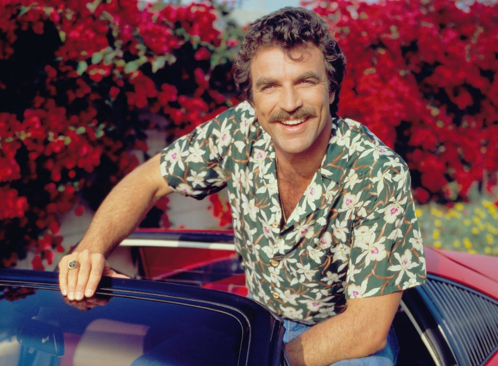 Tom Selleck sits in a red Ferrari 308 for the CBS TV series 'Magnum, P.I.' in January 1984