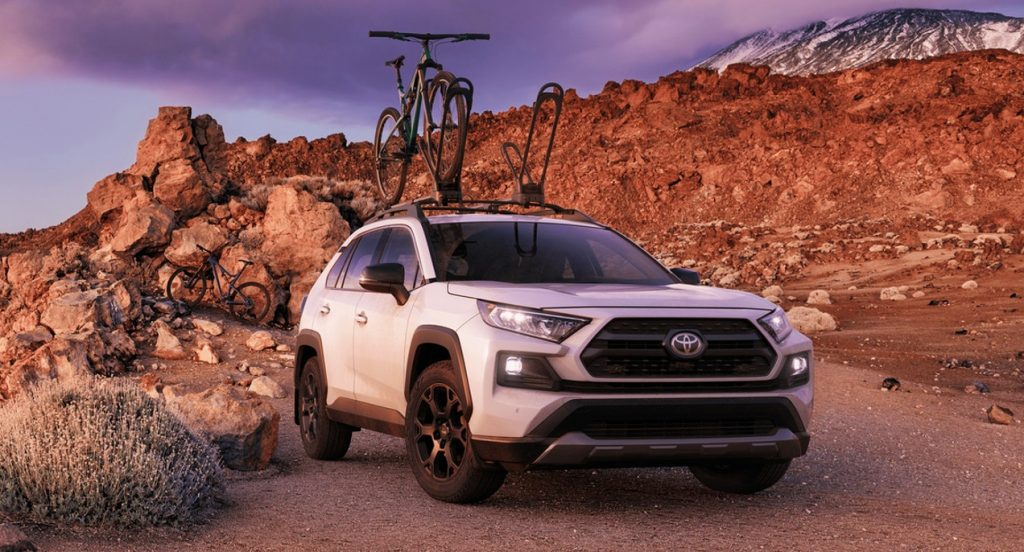 A white Toyota RAV4 TRD Off-Road SUV is parked in a mountainous region. One bike is loaded atop the SUV. Another bike is in the background.