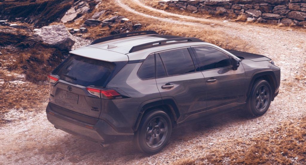 A gray 2021 Toyota Rav4 TRD Off-Road. is on a trail. Rocks and a winding trail leading to a steep hill are in the background.