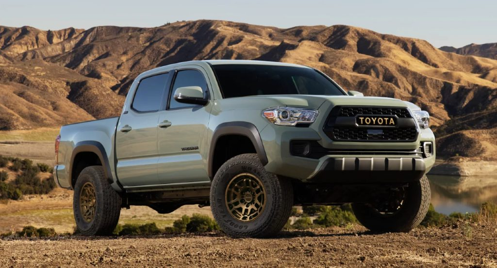 A green Toyota Tacoma pickup truck is parked on dirt.