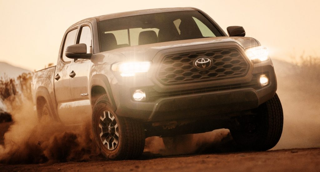 A gray Toyota Tacoma pickup truck is kicking up dust off-roading.