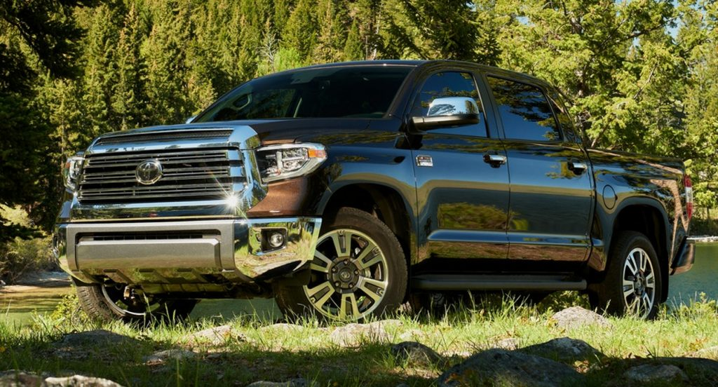 A black Toyota Tundra pickup truck is parked on the grass with trees in the background.
