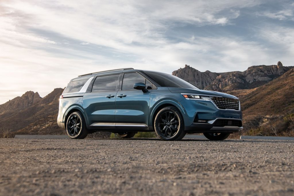 Turquoise 2022 Kia Carnival with mountains in the background