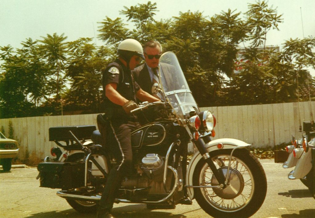 Two Los Angeles police officers look over a Moto Guzzi Eldorado 850 police bike in a 1970s parking lot